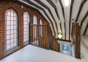 top-of-back-stairs-with-old-ceiling-and-arched-windows